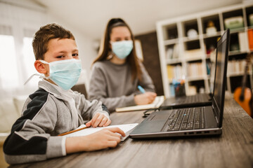 Foto auf Leinwand Dinosaurier Boy and girl studies at home, wear protective masks, and doing school homework. Distance learning online education.