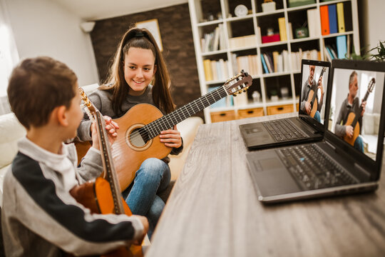 Boy and girl playing acoustic guitar and watching online course on laptop while practicing at home. Online training, online classes.