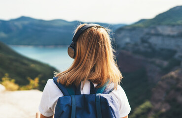 back view girl tourist with light hair dreams listening to music in headphones standing on top of mountains, blonde hipster with backpack walking lake valley and green summer hills, copy space