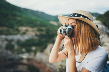Wall Mural - young blonde girl in summer hat take photo on retro camera on background green mountain landscape, hipster tourist enjoys hobby of photographer relax in nature on weekend, empty space