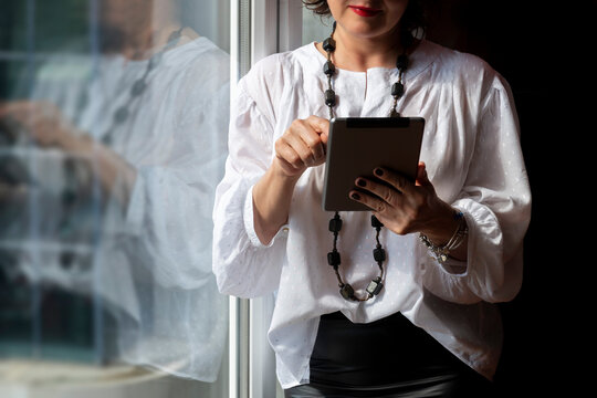 Businesswoman sitting and looking to tablet for checking reports in a cosy office.