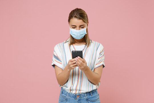 Young woman girl in casual striped shirt sterile face mask isolated on pink background. Epidemic pandemic coronavirus 2019-ncov sars covid-19 flu virus concept. Using mobile phone, typing sms message.
