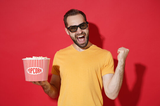 Screaming young bearded man guy in casual yellow t-shirt 3d glasses isolated on red background. People in cinema, lifestyle concept. Watching movie film holding bucket of popcorn doing winner gesture.