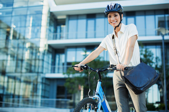 Businesswoman with bicycle outside urban building