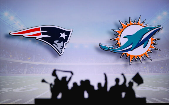 New England Patriots vs. Miami Dolphins. Fans support on NFL Game. Silhouette of supporters, big screen with two rivals in background.