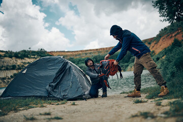 Two men on camping trip putting backpacks into tent by the lake on rainy and cold weather.