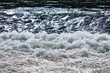 Sprudelnder Fluss mit Stromschnellen an kleinem Wasserfall