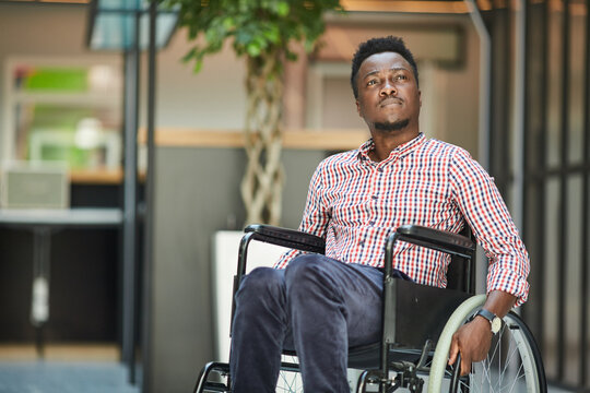 African disabled office worker sitting in wheelchair he is at office building