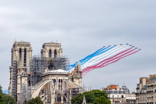 Paris, France - July 14 2019: Bastille Day Aircrafts Parade over Notre Dame de Paris - this is the French Acrobatic Patrol (also known as the Patrouille de France).