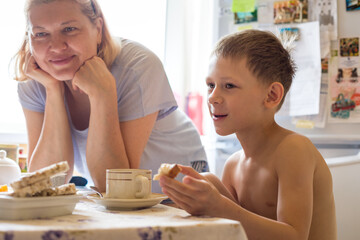 Grandma and grandson have fun talking, having Breakfast in the kitchen.