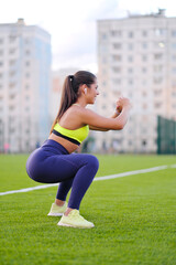 A young beautiful dark-cheeked woman in sportswear is engaged in fitness at the city stadium outdoors. A green football field.