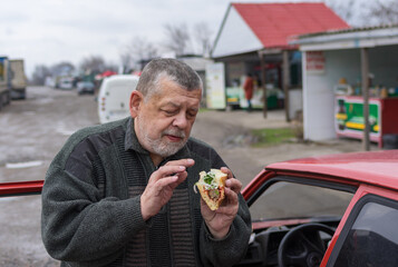 Senior driver holding street food (lyulya kebab in lavash) near his car while standing on a back road in Ukraine