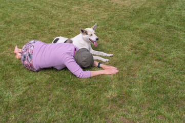 Mature Caucasian woman and  young white mixed breed dog lying on a cut lawn at summer season