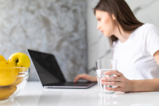 Woman drinking from water glass while typing at her laptop. Thirsty woman staying hydrated while working from home