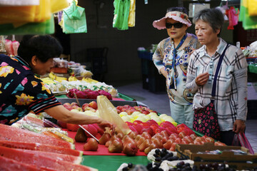 Women buy fruits at a market in Taipei