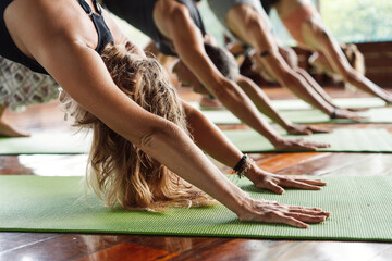 Yoga class in a tropical environment of a yoga meditation retreat. Hands close up