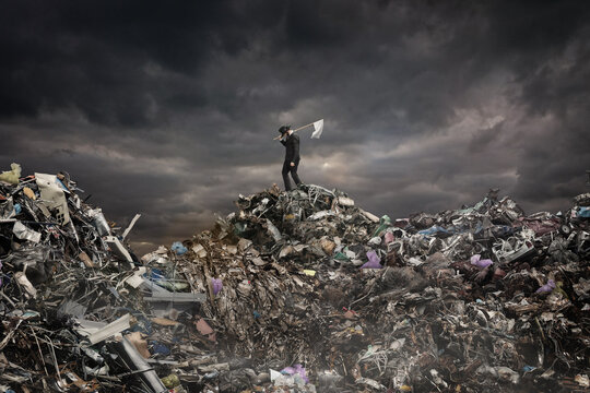 Global warming concept. A man with a white flag stands on a mountain of garbage on a gloomy background.
