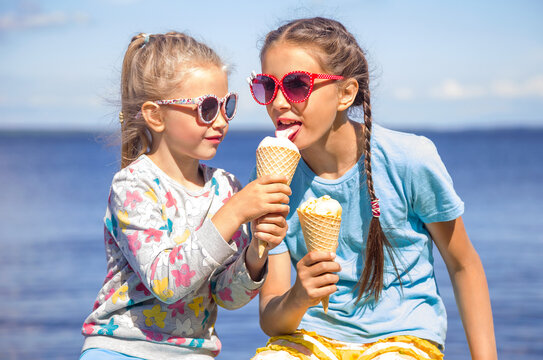 Two adorable little girls wearing sunglasses are eating ice cream on the seashore on summer vacation. Small girl is sharing her ice cream with sister