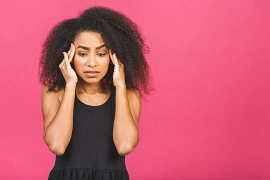 Nervous african woman breathing calming down relieving headache or managing stress, black girl feeling stressed massaging temples exhaling isolated on pink background.