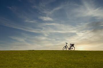 Ein Fahrrad steht oben auf einem Deich mit Abendhimmel