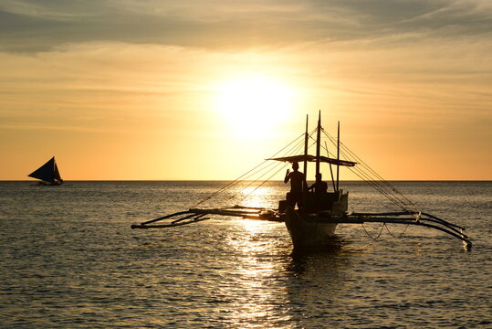 Fishing boat silhouette at sunset. Boracay island. Western Visayas. Philippines