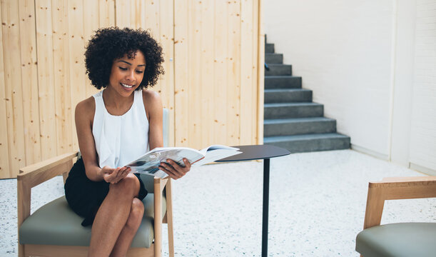 Cheerful busy woman reading journal