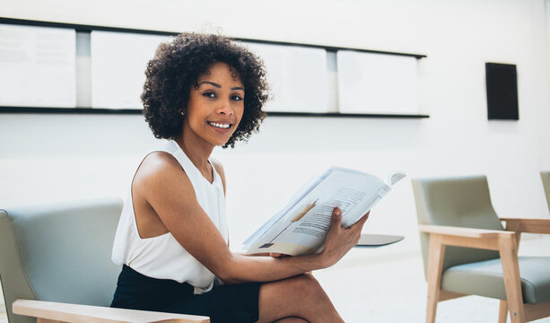 Charming dark skinned female entrepreneur spending free time in office holding newspaper with financial articles,prosperous african american businesswoman looking at camera hold magazine