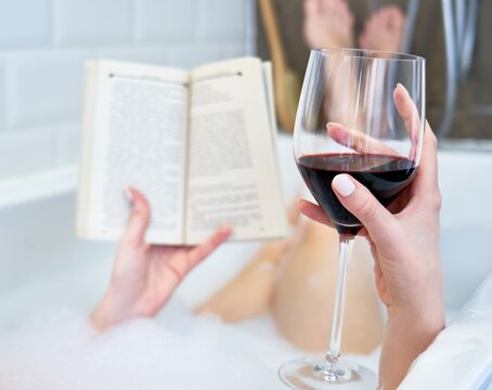 Back view of woman holding a glass of red wine and reading book in bath with foam.