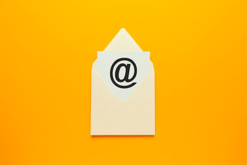 Envelope with e-mail symbol on yellow background, concept of corporate communication and marketing...