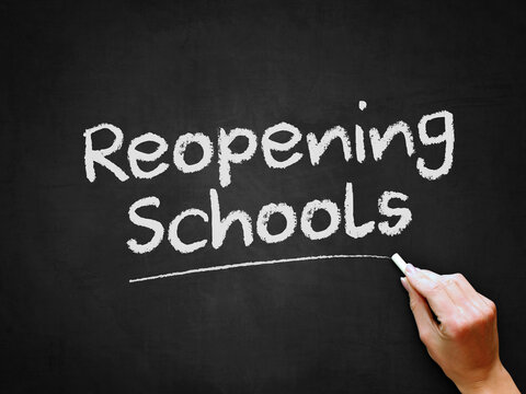 A hand writing 'Reopening Schools' on chalk board for schools reopening plans after Covid-19 (Coronavirus) pandemic lockdown.