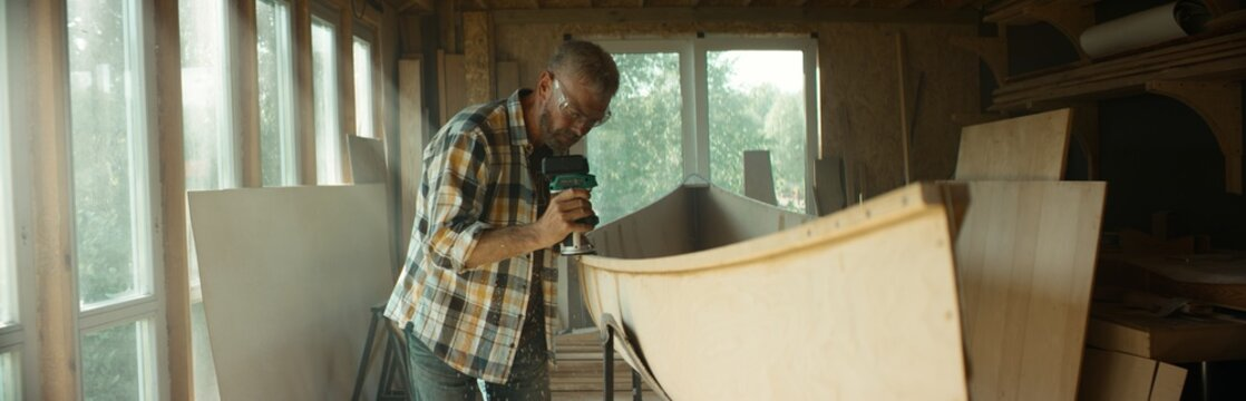 Mid 50s Caucasian male building a canoe in his workshop, using milling tool. Boat making hobby, small business owner