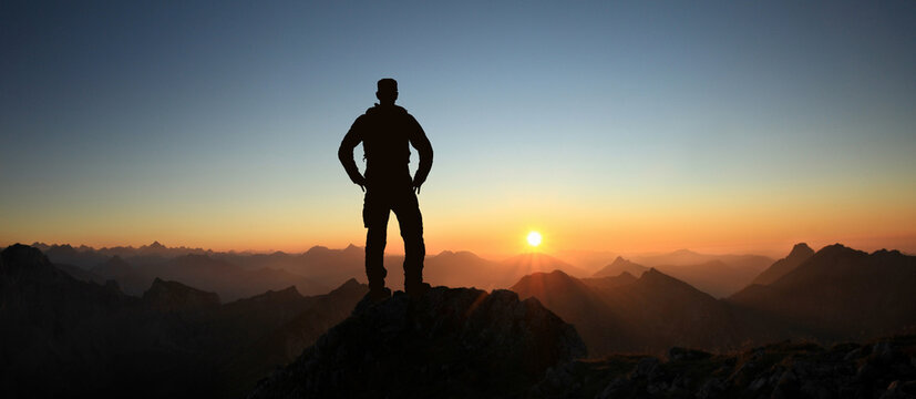 Man Silhouette reaching summit enjoying freedom and looking towards mountains sunset. Allgau Alps, Bavaria, Germany and Tyrol Austria.