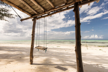 Beautiful swing with blue sky and white clouds in background, Zanzibar, Tanzania..