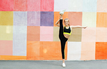 Fitness sport young girl in sportswear doing yoga fitness exercise on a wall background. Sporty...