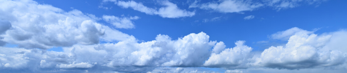 July is the summer sky. Panoramic photo of dense, brightly white clouds flying low above the ground. Fototapete