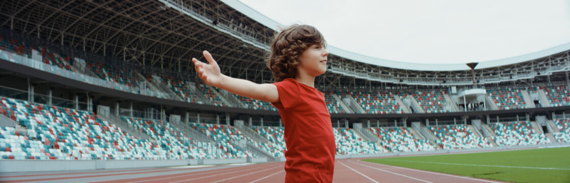 Cute little kid boy soccer player spreading his hands on an empty stadium, dreaming of becoming professional player, soccer star