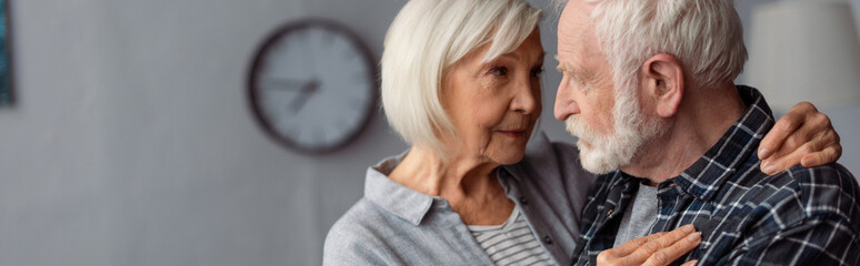 panoramic crop of senior woman hugging husband, sick on dementia, while standing face to face