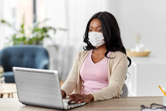quarantine, remote job and pandemic concept - african american woman wearing face protective medical mask for protection from virus disease with laptop computer working at home office