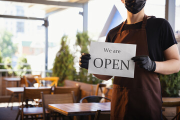The waiter works in a restaurant in a medical mask, gloves during coronavirus pandemic. Representing new normal of service and safety. Holding board with words WE ARE OPEN. Taking care of clients.