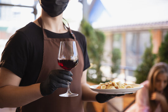 The waiter works in a restaurant in a medical mask, gloves during coronavirus pandemic. Representing new normal of service and safety. Putting the order, meals and drink, wine. Close up.