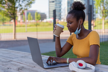 young black woman at work on her laptop in time of epidemic outdoors, use of protective mask, young student in the park sipping her cappuccino coffee
