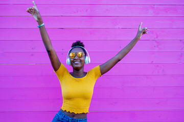 black woman dancing and smiling, pink background in contrast with yellow clothes and jeans, afro fashion girl with headphones to listen to music, silent disco and new normal, social distancing
