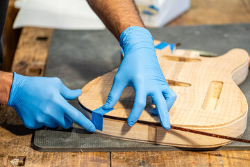close-up of a luthier's hands at work on the body of a guitar, hands of a craftsman with protective gloves, music business and construction of musical instruments