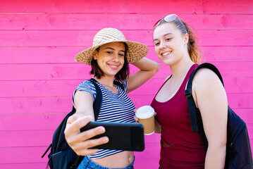two young women explorers of the city make themselves a selfie, travelers in the city equipped with backpacks, smart phones and take-away coffee