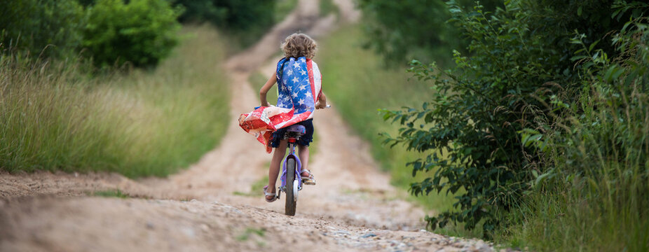 Symbol of celebration 4 fourth of july. Young Girl riding bicycle with american flag in hand