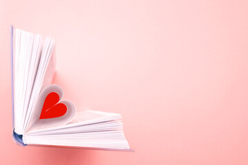 Pages of book curved into a heart shape on pink backdrop. Flat lay, empty space for text. Educational concept for school, bookshop, love for literature, Valentine's Day greeting