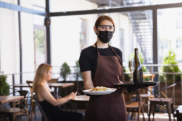The waitress works in a restaurant in a medical mask, gloves during coronavirus pandemic....