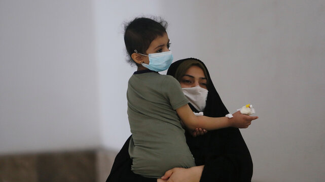 An Iraqi woman wearing a protective mask carries her daughter who suffers from cancer at the Children's Hospital for Cancer Diseases in Basra