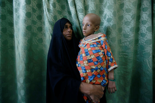 An Iraqi woman carries her daughter who suffers from cancer at the Children's Hospital for Cancer Diseases in Basra