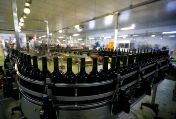 Bottles of wine await labelling on a production line at Nederburg Wine Estate in Paarl